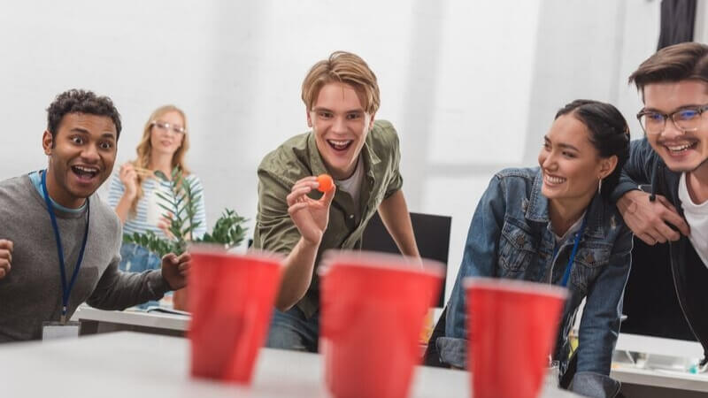 Staff playing beer pong in their office for a corporate Christmas event