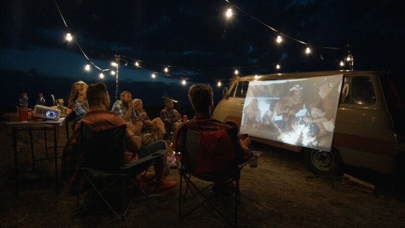 Staff gathering in a team member's garden with a DIY cinema screen for their corporate Christmas event